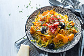Pumpkin spaghetti with pumpkin ragout, tomatoes, olives and Parmesan cheese