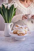 Windbeutel mit Cremefüllung und Sahne, im Hintergrund Frau mit Kaffeetasse