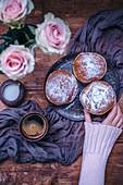 Frauenhand greift nach Krapfen auf Kaffeetisch mit Rosenstrauß