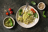 Classic italian spaghetti pasta with pesto sauce, pine nuts, olive oil and fresh basil