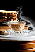 Dampfende Tasse Chai Latte serviert mit Kuchen
