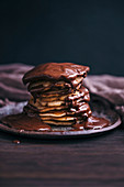 Stack of banana pancakes drizzled with melted chocolate