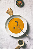 Autumn pumpkin cream soup on white tablecloth, top view
