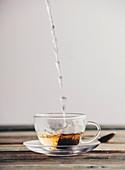 Heißes Wasser wird in Glastasse mit Teebeutel gegossen