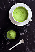 A cup of Matcha green tea with a small of bowl of Matcha tea powder and a spoon