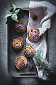 Fresh herbs and piece of cloth lying on tray with yummy cinnamon rolls on gray surface
