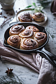 Frying pan with tasty fresh cinnamon rolls placed near napkin on marble tabletop