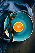Fresh orange in a teal plate on dark background