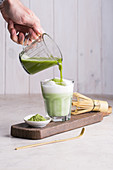 Preparing matcha latte beverage
