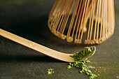 Green matcha tea powder and bamboo whisk