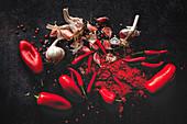 Frische rote Chilischoten, Chilipulver und Knoblauch