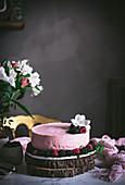 Erdbeermoussetorte mit Blumendeko auf Marmortisch