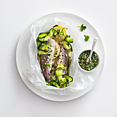 Hake with zucchini and lemon in paper, served with salsa verde