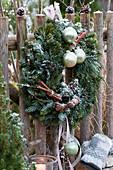 Weihnachtlich geschmückter Kranz am Gartenzaun