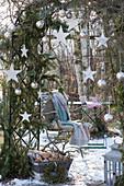 Sitzplatz unterm weihnachtlich dekorierten Rosenbogen