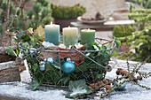 Drahtkorb mit Kerzen, Kugeln und Efeu als weihnachtliche Dekoration
