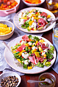 Salad with mozzarella, prosciutto and mango plus chili dressing