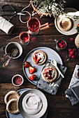 Cake tartlets with vanilla pudding and strawberries on a rustic table