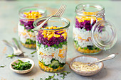 Layered salads with vegetables, ham, eggs and mayonnaise sauce in glasses