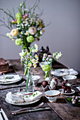 A table laid for Easter with spring flowers and chocolate eggs