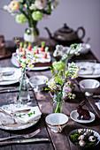 Gedeckter Ostertisch mit Frühlingsblumen und Schokohase