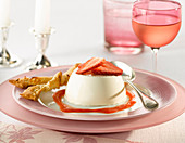 Strawberry panna cotta with a filo pastry twist and coulis with a glass of rose wine