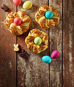 Easter bread nests with colourful Easter eggs on an old brown wooden surface