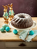 A Bundt cake dusted with icing sugar with Easter decorations