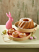 A Bundt cake and mini Bundt cakes dusted with icing sugar with Easter decorations
