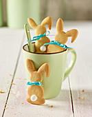 Kekse in Hasenform in Kaffeetasse auf weißem Holztisch