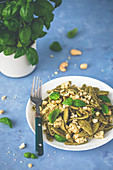 Spinach pasta with pesto, tofu and nuts