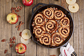 Apple pecan sticky buns with caramel sauce in a cast iron pan
