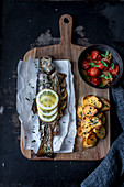 Oven-roasted brook trout with baked potatoes and tomato and onion sauce