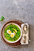 A smoothie bowl with boiled egg, avocado and mange tout in a nest of herbs