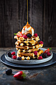 Belgian waffles topped with ice cream, berries and caramel sauce