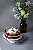 Carrot cake with coconut chips, cream cheese and quark cream and edible flowers for an Easter breakfast