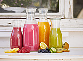 Various smoothies in glass bottles on a window sill