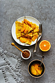 Crepes Suzette on plate flat lay. Thin pancakes with orange sauce over grey concrete table background