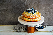 Meringue Pavlova cake on cake stand with blueberry and mascarpone cream