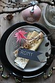 Weihnachtsgedeck mit goldener Serviette, Namensschild und Reagenzglas mit goldenen Perlen