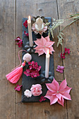 Arrangement of paper flowers and grey candles on slate board decorating tablw