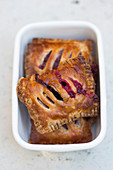 Rustic cherry hand pies in a white enamel tin