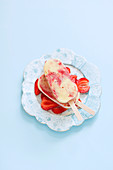Two strawberry and custard popsicles on an old porcelain plate with strawberry slices