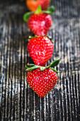 Erdbeeren hintereinander aufgereiht auf Holzuntergrund