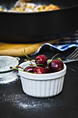 A bowl of fresh cherries next to a sieve of icing sugar