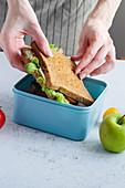 Hände legen Sandwich mit Schinken, Tomaten und Käse in Lunchbox