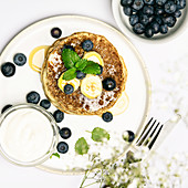 Banana oat pancakes with fruits, berries and maple syrup