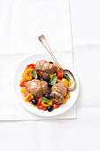 Boneless turkey legs on peppers and olives with rosé wine