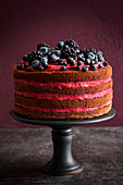 A naked layer cake with dark berries