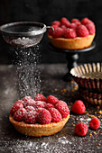 A raspberry tartlet being dusted with icing sugar